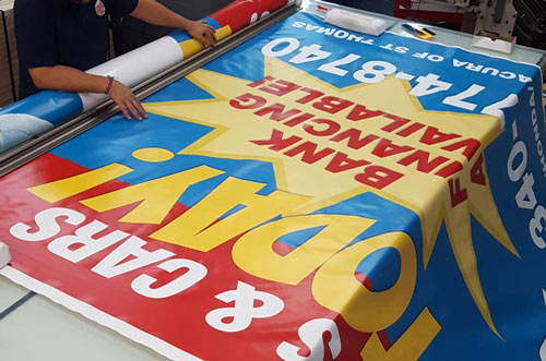 The picture shows an 8ft-wide custom vinyl banner that is being manufactured on a large work table. Grommets and hems are being added to the vinyl banner